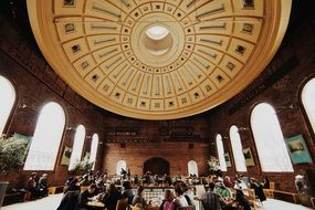 people in hall with brick walls under impressive dome