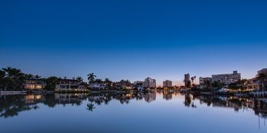 evening skyline of tropical citiy with reflection on water