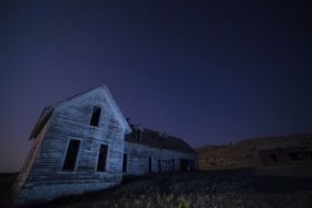 old house stands on a hill at night