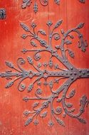forged ornament on red wooden door