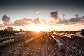 cargo trains on railway near station at sunset