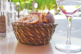 breadbasket with bread on table in open air restaurant