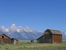 old wooden farm buildings on meadow at mountains, usa, wyoming, grand tetons