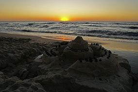 sand castle on the beach with sea sunset