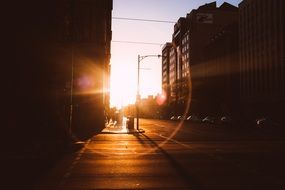 sunset flare above street in city