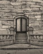 arched entrance door in old stone wall