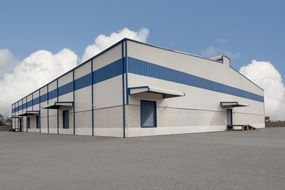 blue white industrial building construction sky clouds