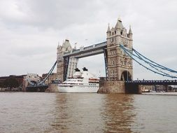 cruise ship on thames river under tower bridge, uk, england, london