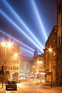 orange lamps on street and blue rays of light at dark sky above city