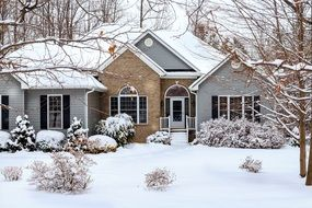 snow covered front yard of brick village house