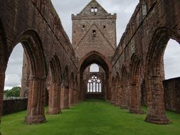 sweetheart abbey ruin at cloudy sky, uk, scotland