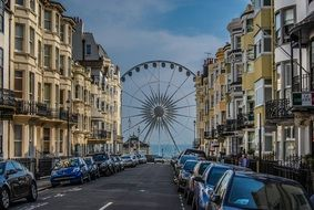 ferris wheel at sea in perspective of old street, uk, england, brighton