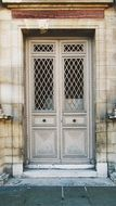 old wooden door with metel grated windows in stone facade, france, paris