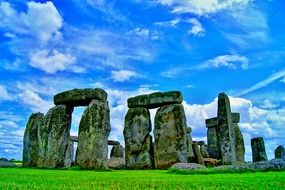 giant mossy stones at circle, stonehenge on green grass at blue sky, uk, england