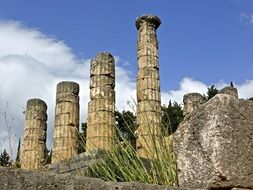 ruins roman ancient rock columns clouds blue sky view