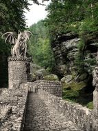 winged cat, stone sculpture on medieval castle ruins in forest, collage