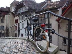 bicycle with basket stands at fence on cobblestone pavement in old town, switzerland, aarau