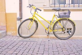 yellow bike with basket stands on pavement at facade