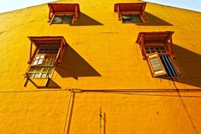 windows with shelters on orange facade