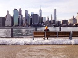 young boy sits on bench at new york city skyline, usa, manhattan