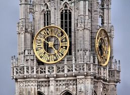 golden clock on gothic cathedral tower, netherlands, antwerpen