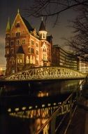 speicherstadt at night, illuminated bridge and building in hatbour, germany, hamburg