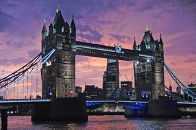 tower bridge across thames river at purple evening sky, uk, london