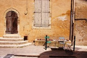 chairs at facade of old stone building with wooden door, france, provence