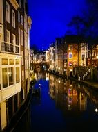 colorful illuminated facades reflecting on canal at dusk, netherlands, utrecht