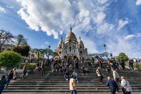 The staircase is filled with people near the cathedral in paris