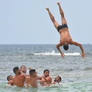 jumping man above happy young men in sea