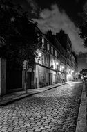 old houses at dark street with cobblestone pavement, france, paris