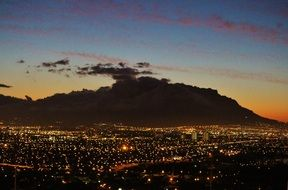 city lights at dark table mountain at sunset, south africa, cape town