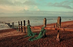 weathered wooden fence on seashore, uk, sussex, rye