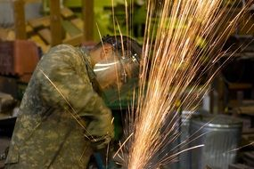 A man in a hardhat working with metal, process of welding