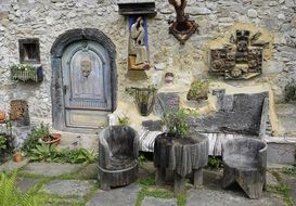 handmade wooden furniture at old ornamented stone wall