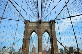 view of new york city througt brooklyn bridge constructions, usa