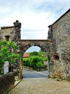 view of green village through arched gateway in medieval stone wall, france, pérouges