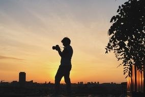 photographer, silhouette with camera at evening sky