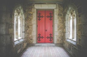red door in old stone wall with gothic windows