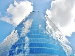 clouds in sky with reflections on tower building facade