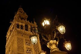 antique street lantern in front of cathedrale at night, spain, seville