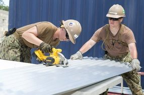 two women at work, construction workers cutting waved roofing sheet
