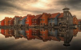 row of colorful houses with mirroring on water, netherlands, Reitdiephaven