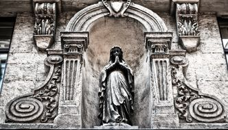 stone carving and praying woman sculpture on facade of old building