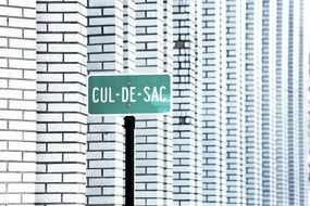 cul de sac street green sign white bricks