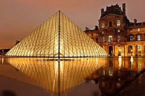night view of louvre pyramid with reflection on water, france, paris