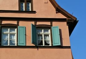 windows with open green shutters on facade of old house, germany, bamberg