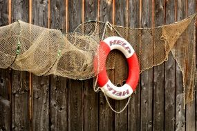 fishing net and lifebelt on a wooden wall