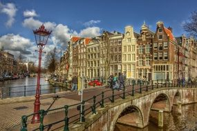 people walking on pedestrian bridge across channel in beautiful old city, netherlands, amsterdam, keizersgracht